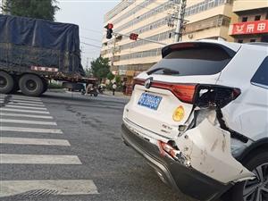 白色长安轿车与两辆挂车碰撞,车辆碎片散落一地